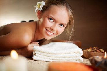 Portrait of happy young female looking at camera in spa salon