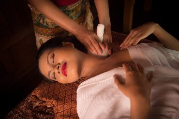 Masseur doing massage on Asian woman body in the spa salon
